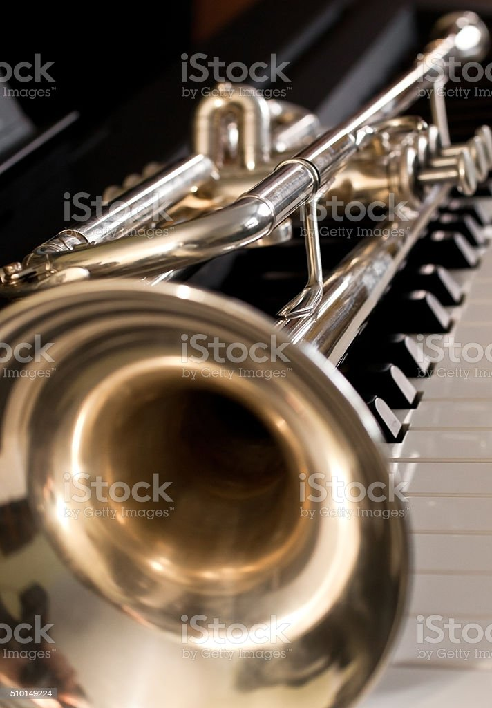 Fragment of a trumpet on the keys of the piano stock photo