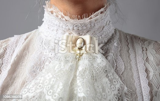 Fragment of a Victorian dress with a brooch. White blouse with lace, embroidery and high collar.