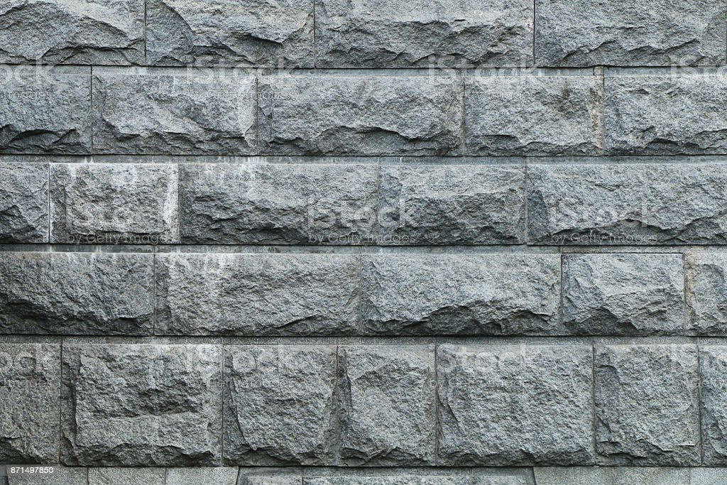 Fragment of a wall from a gray granite stone stock photo