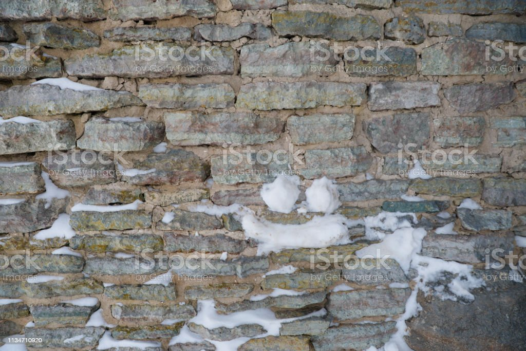 Fragment of an old fortress wall with traces of snow as the basis of...