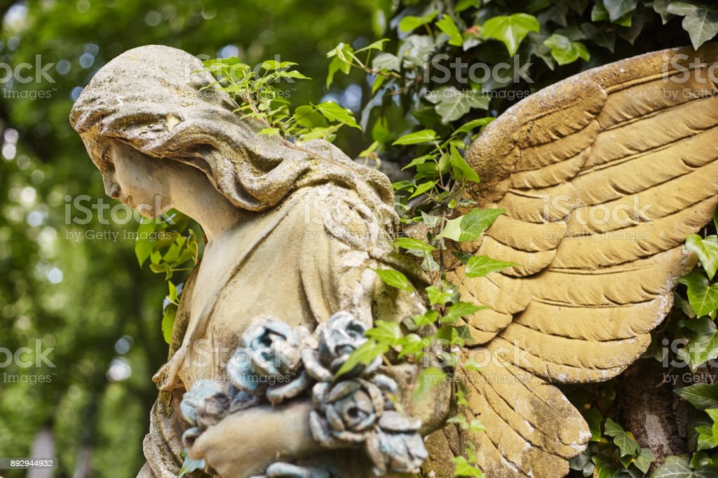 A fragment of ancient sculpture angel in a golden glow in the old cemetery. stock photo