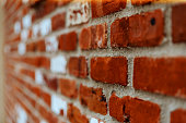 Fragment of brown brick wall with a shallow depth of field, at an angle to the plane. Selective focus.