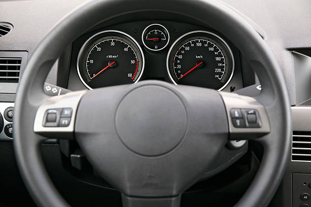 Fragment of car dashboard with steering wheel and meters Close-up of a car dashboard, focus is on the meters dashboard vehicle part stock pictures, royalty-free photos & images