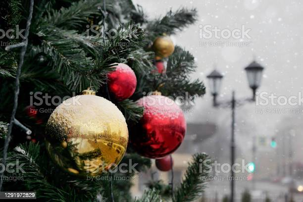 Photo of Fragment of Christmas tree decorated with red and yellow balls lightly covered with snow
