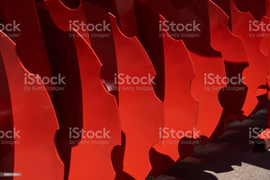 Fragment of cultivator with red working disks stock photo