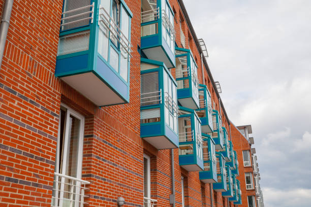 Fragment of new brick building wall with windows and blue balconies. Modern apartment house. stock photo