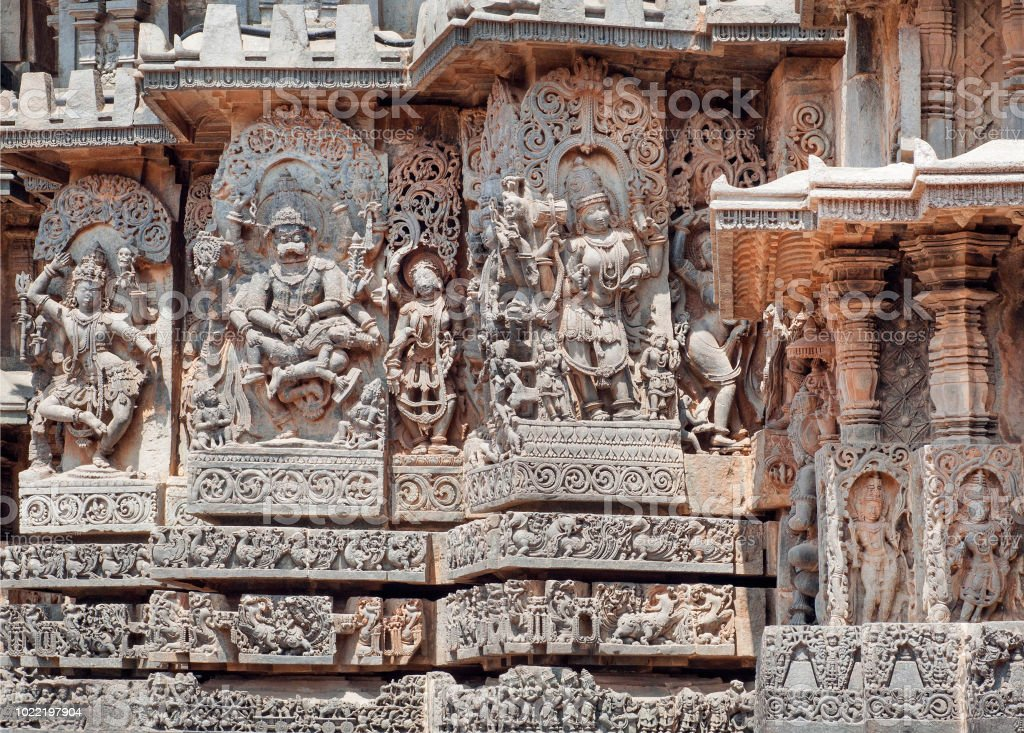 Fragment of stone carved relief with Kali, Narasimha and other Hindu gods. 12th century South Indian temple. Halebidu heritage, India stock photo