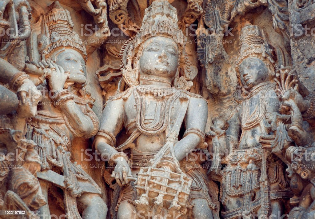 Fragment of stone carved relief with musicians playing music of gods. 12th century South Indian temple. Halebidu heritage, India stock photo