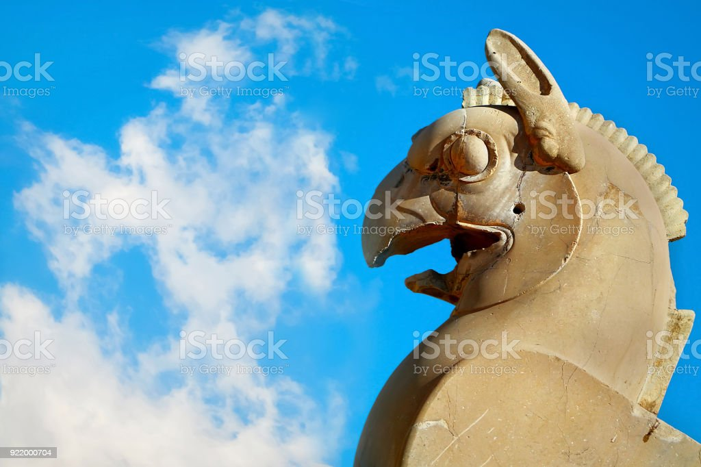 Fragment of stone column sculpture of a Griffin in Persepolis against a blue sky with clouds. Ancient Achaemenid Kingdom. Iran. Persia. stock photo