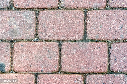 Fragment of the pavement, paved with stone blocks of pink color for use as an abstract background.
