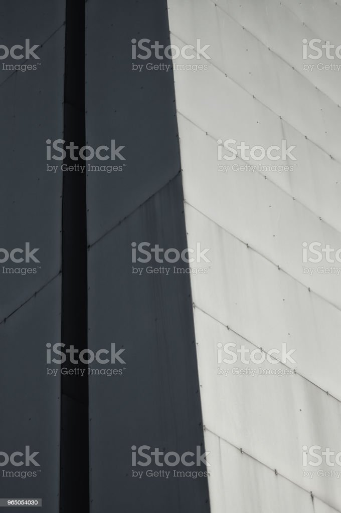 Fragment of the angle of modern high-rise structure in gray color for background or texture in design royalty-free stock photo