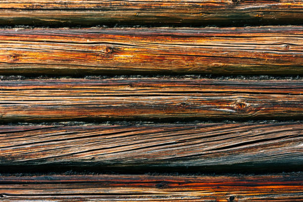 Fragment of the facade of a log wall. Rustic log wall horizontal wood background. Fragment of unpainted wooden debarked logs of a barn or house wall. Copy space stock photo