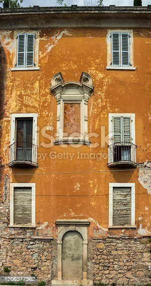 Fragment of the facade of an old house. The mural on the wall. Italy. Soft focus.