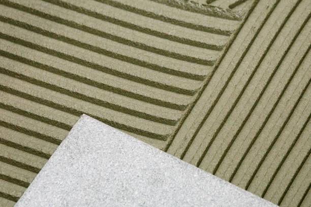 fragment des bodens bei der verlegung von keramischer fliesen, close-up. - fliesenkleber stock-fotos und bilder