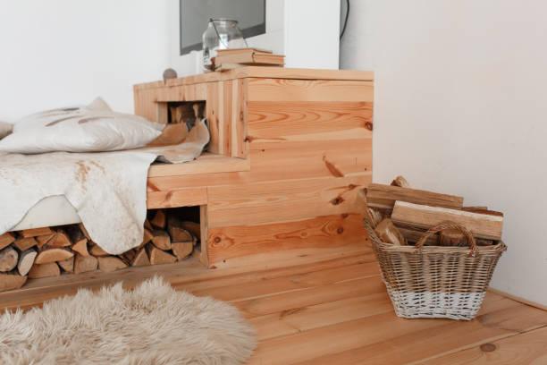 fragment des innenraums eines landhauses. holzbett und brennholz unter ihm, korb voller brennholz - jagdthema schlafzimmer stock-fotos und bilder