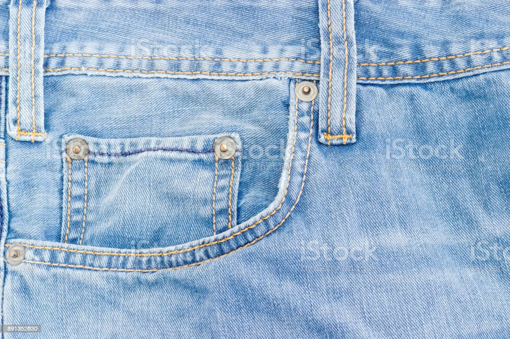 Fragment of the top of the old light blue jeans stock photo
