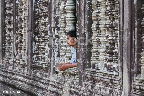 Siem Reap, Cambodia - November 29, 2016: Fragment of the wall of the Hindu temple complex of Angkor Wat. A man with a phone in his hands looks out of the window.