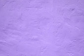 Fragment of wall covered with gypsum with traces of spatula in ultra violet tones, Ultra Violet color - Pantone Color of the Year 2018, style and fashion