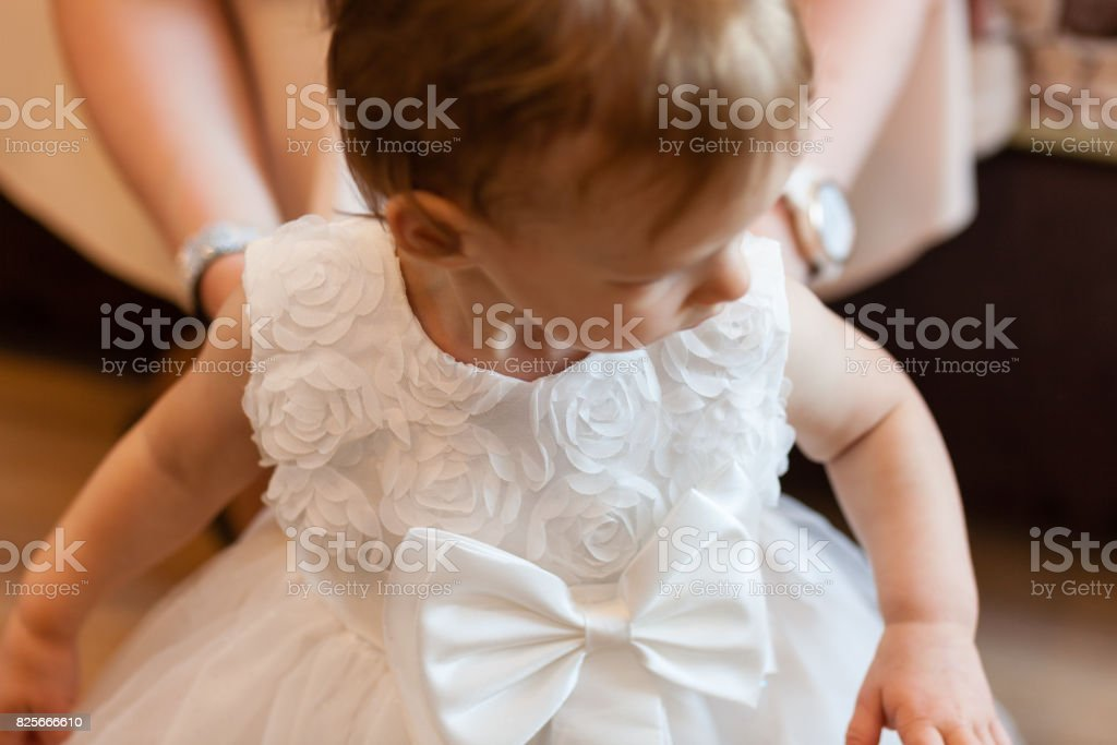 Fragment photo of little baby girl preparing for christening ceremony, hand on a white dress, baby girl on christening day. stock photo