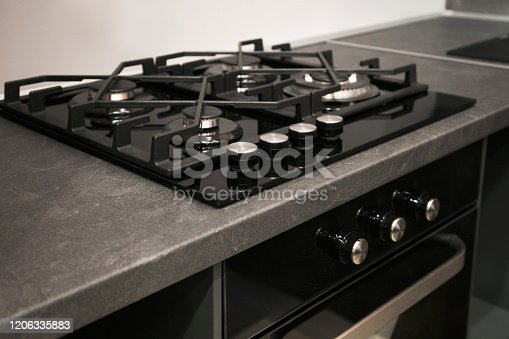 Fragment of the stainless cooking plate. The steel gas hob detail on black stone worktop.