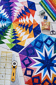 Fragments of quilt, accessories for patchwork, top view on a white wooden surface