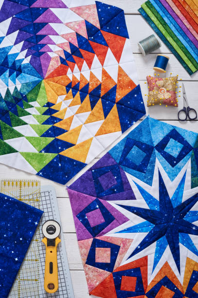 fragments of quilt, accessories for patchwork, top view on a white wooden surface - quilt stock photos and pictures