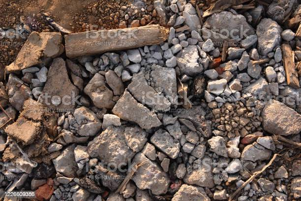 Photo of fragments of stones mixed with debris, pieces of old cloth are lying, debris from wood and dirt