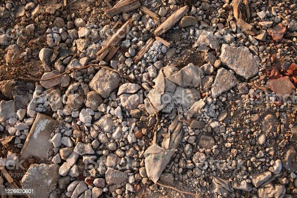 Photo of fragments of stones, the texture of nature mixed with garbage, pieces of old fabric, rubbish from wood and dirt lie