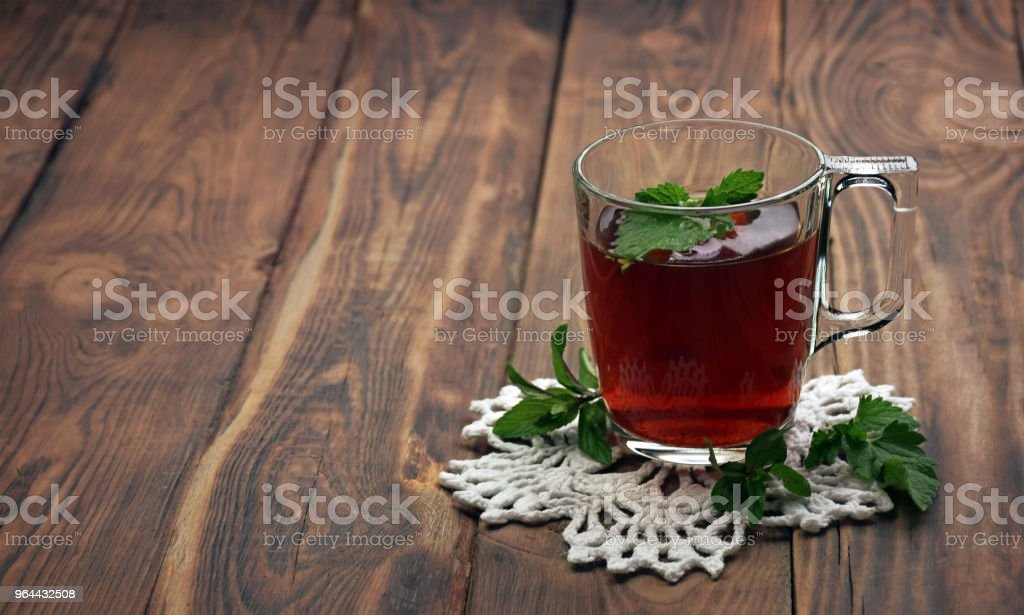 A fragrant herbal tea with mint leaves, lemon balm, raspberries and currants. Close-up. A cup of herbal tea on a wooden background. - Royalty-free Antioxidant Stock Photo