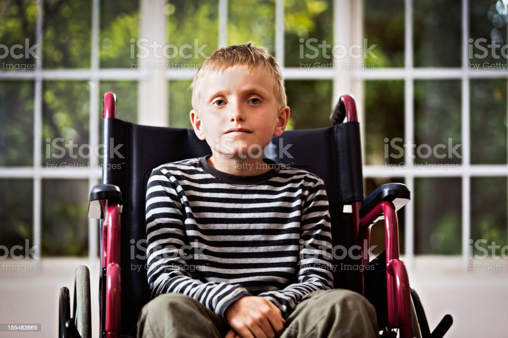 Frail blond boy in wheelchair bravely tries to smile stock photo