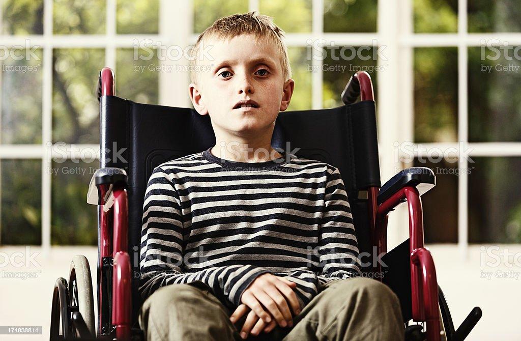 Frail little boy sitting in wheelchair looks worried stock photo