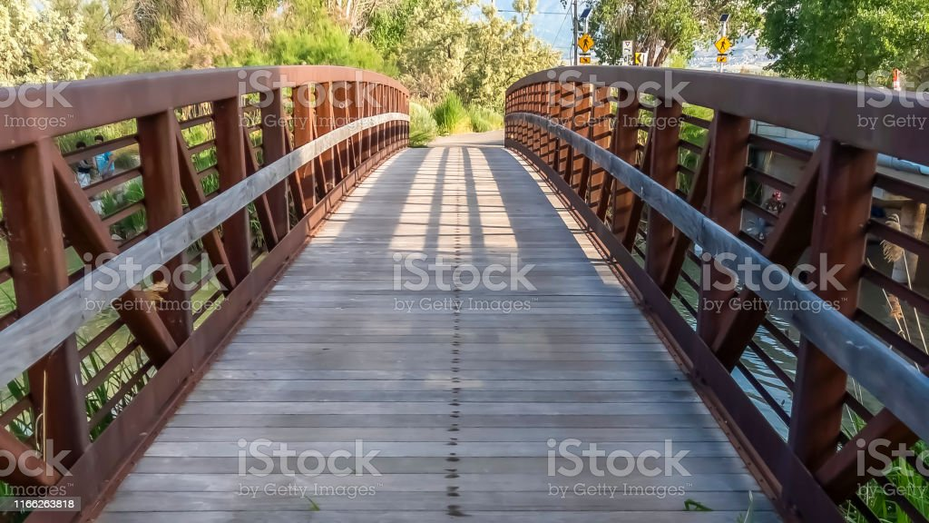Panorama frame Bridge with wood deck and rusty metal railing over a...