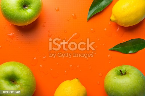 istock Frame composition from fresh raw green organic apples juicy lemons leaves on orange background. Healthy lifestyle vitamins detox balanced diet clean eating vegan concept. Copy space 1093381648