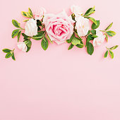 istock Frame composition with pink roses and leaves on pastel pink background. Flat lay, top view. 1062020858