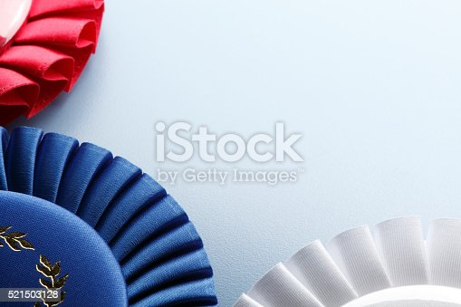 A close up of a rosette of a first place blue ribbon surrounded by a white ribbon and a red ribbon.  Ample copy space created by the light blue background.