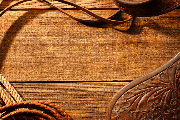 frame created by horse riding tack on rustic brown wood - wild west stock photos and pictures