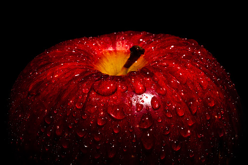 A Frame filling Macro image of a vibrant Red apple covered in water drops beading on the peel.  This is a high contrast image with a strong highlight on the front of the fruit.  Featuring  1/3 frame of negative space in black above the apple for copy writ