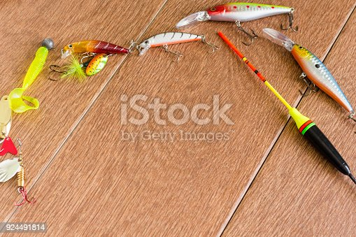 istock Frame fishing tackle - fishing spinning, hooks and lures on light wooden background. Top view 924491814