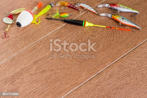 istock Frame fishing tackle - fishing spinning, hooks and lures on light wooden background. Top view 924741650