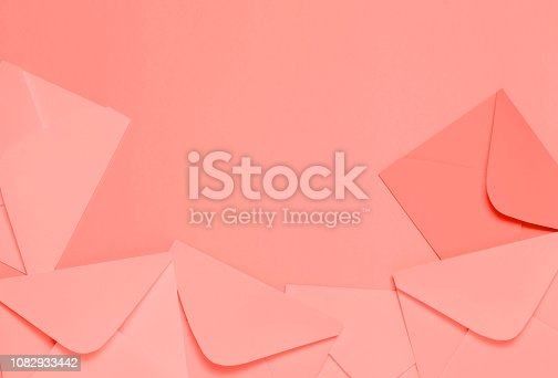 968272356istockphoto Frame from colorful envelopes on living coral table top view. 1082933442
