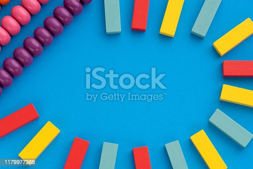 istock Frame from kids toys, top view on children's educational games on blue paper background. Multicolored wooden bricks, abacus. Flat lay, copy space for text 1179977368