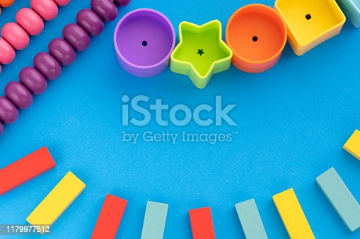 istock Frame from kids toys, top view on children's educational games on blue paper background. Multicolored wooden bricks, abacus, circles, stars. Flat lay, copy space for text 1179977512