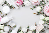 istock Frame from natural cosmetic and flowers on pastel table top view. 985057782