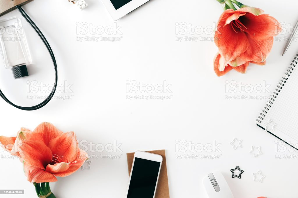 Frame from tablet, notebook, pen, flowers amaryllis, smart phone, bag, computer mouse and perfume. Top view. Flat lay. Home office womens fashion workspace white background. Office table desk - Royalty-free Adult Stock Photo