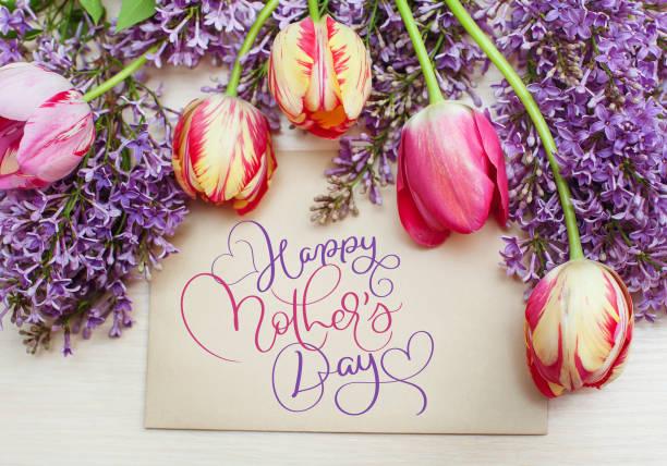 rahmen von tulpen und flieder und text happy muttertag. kalligraphie-schriftzug hand zeichnen - hochzeitsspiele eltern stock-fotos und bilder