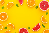 summer flatlay background. Bright citrus composition from grapefruit, orange, mint leaves and a straws on bright yellow background. Summer flat lay pattern
