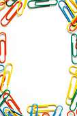 Frame made of multi colored paper clips isolated on a white background. Space for copy inside.
