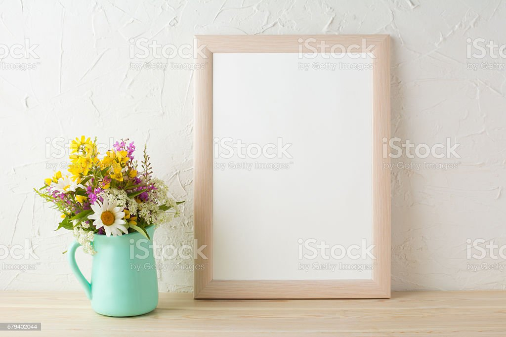 Frame mockup with flowers in mint green vase stock photo