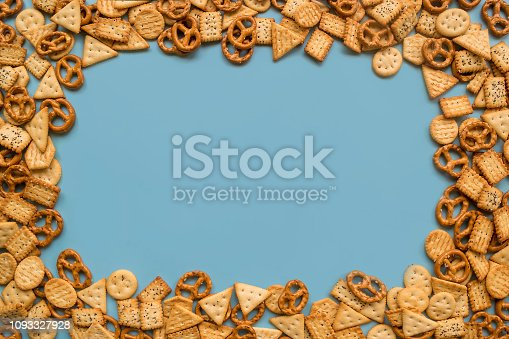 istock Frame of a lot of mini crackers with poppy seeds and salt crystals on a blue background, flat lay 1093327928