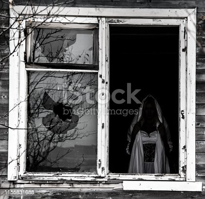 Frame of an old window with a scary white silhouette